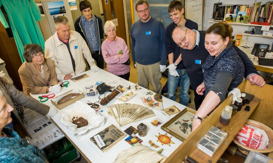 Photo of staff and visitors looking at artefacts on a table