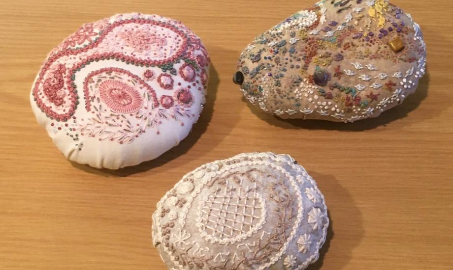 image of 3 oval shaped stones covered in seaside themed embroidered pictures