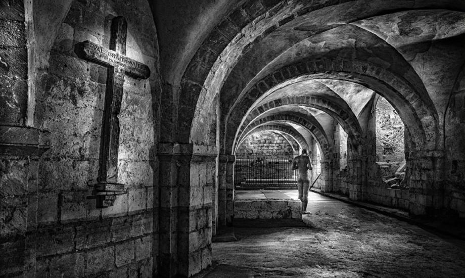 black and white image of the crypt at Winchester cathedral with statue of person and a crucifix on the wall