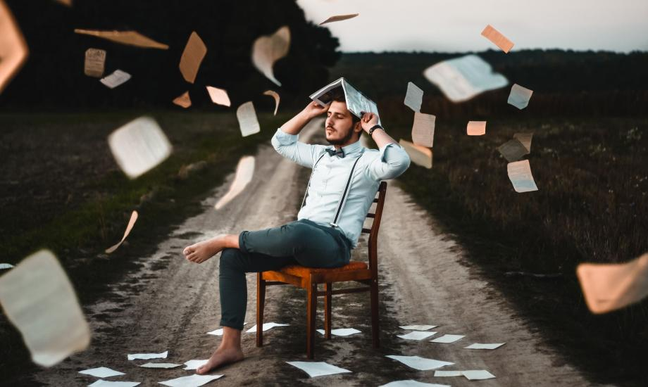 man surrounded by floating books