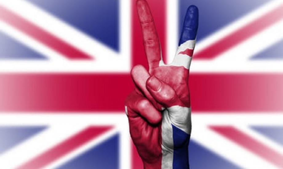 Image of British flag with V for victory sign by a hand in foreground