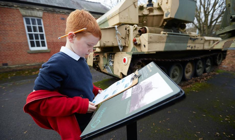 Boy in front of tank