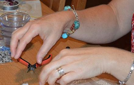 Image of hands making beaded jewellery in a workshop