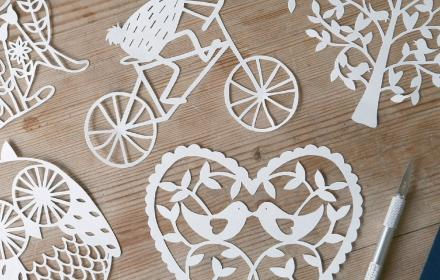 papercut heart, tree and rabbit on a bicycle